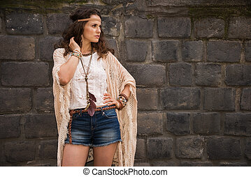 hippy young woman near stone wall looking on copy space -...