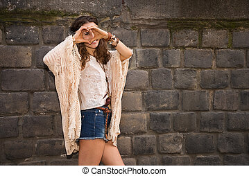 Longhaired hippy young woman near stone wall making heart...