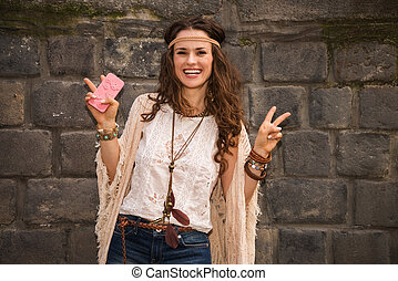 happy boho young woman near stone wall showing victory...