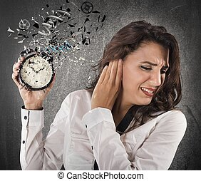 Annoyed by alarm - Woman annoyed by the sound of alarm