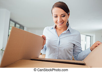 Happy woman unpacking - Happy confident woman unpacking and...
