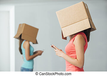 Adolescents and social isolation - Teenager girls with boxes...