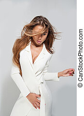 Beautiful woman with full lips poses in white coat -...