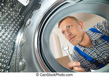Repairman Looking Inside The Washing Machine - Young...