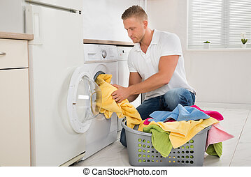 Man Putting Dirty Clothes Into The Washing Machine - Young...