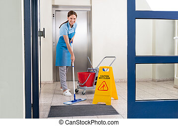 Worker Cleaning Floor With Mop - Happy Female Worker In...