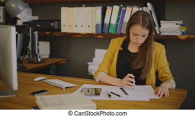 Business Woman Architect drawing checks, measuring compasses...