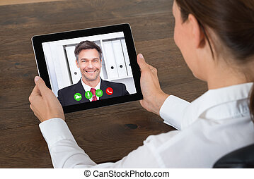 Businesswoman Videochatting On Digital Tablet - Close-up Of...