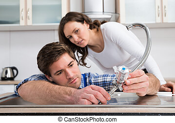Woman Looking At Plumber Fixing Steel Tap - Young Woman...