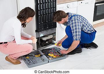 Repairman Repairing Refrigerator - Young Repairman Repairing...