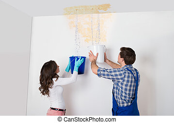 Woman And Repairman Collecting Water From Ceiling - Young...