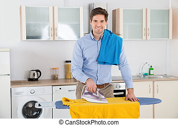 Man Ironing Clothes At Home - Young Man Smiling While...