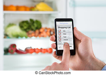 Person Hands Marking Shopping List On Mobile Phone Display -...