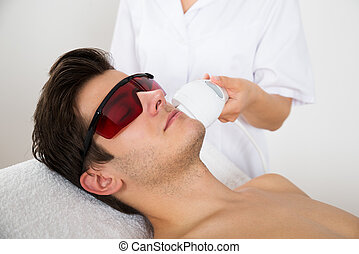 Man Receiving Laser Hair Removal Treatment - Young Man...