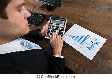 Businessman Analyzing Financial Data With Calculator