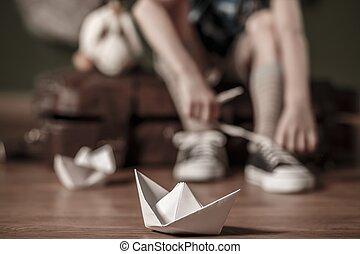 Boy tying shoelaces - Boy sitting on the valise and tying...