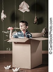 Boy blowing soap bubbles - Boy in carton box blowing soap...