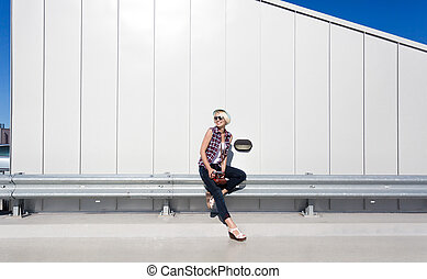 hipster girl sitting on steel protection fence on parking -...