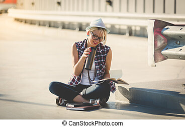 stylish hipster girl sitting on street and reading book -...