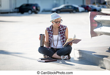stylish woman reading book on street ground and drinking...