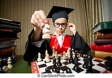 smart girl in graduation cap making move at chess with horse...