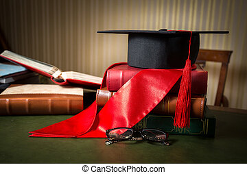 graduation cap and red ribbon lying on books at library -...