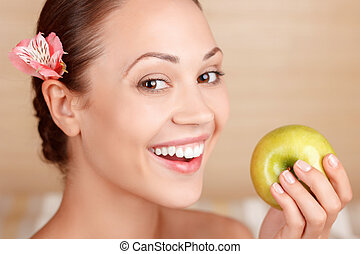 Smiling woman holding apple - Safe and sound. Beautiful...