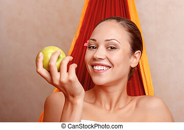 Nice woman sitting in spa salon - Apple per day keeps doctor...
