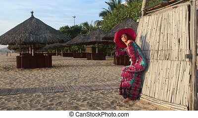 girl in long dress and red hat poses by beach bamboo tower
