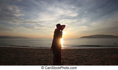 silhouette of girl who admires scenery of sunrise above sea...