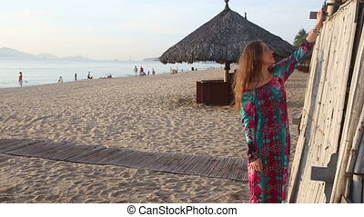 girl in long dress and red hat poses by beach bamboo tower -...