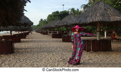 girl in long dress poses on beach at umbrellas and comes