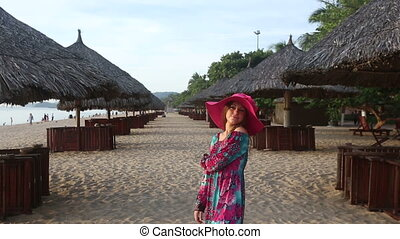 girl in long dress poses on beach at umbrellas and comes back