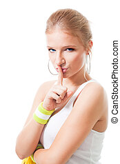 Woman in sport clothes make shh sign, look at camera,...