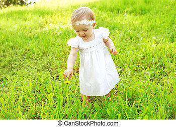 Cute baby walking outdoors on the grass in sunny summer day