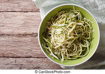 Useful raw zucchini pasta in a bowl close up. horizontal top...