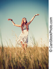 Beautiful young hippie girl dancing in the field at sunset...