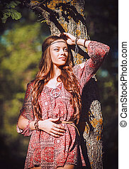 Portrait of beautiful young hippie girl standing near tree -...