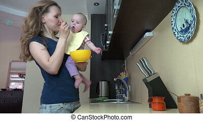 mom feed baby at home - happy young woman feed little baby...