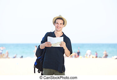 Smiling travel man standing by the beach with map
