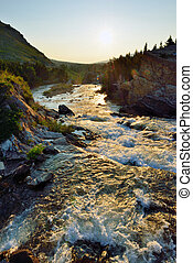 sunset near swiftcurrent lake and whitewater rapids in...