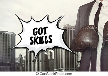 Got skills text with businessman wearing boxing gloves on...