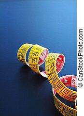 measuring tape - yellow measuring with copyspace on a dark...