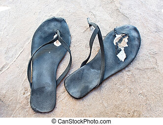Flipflops torn distressed used and broken in black.
