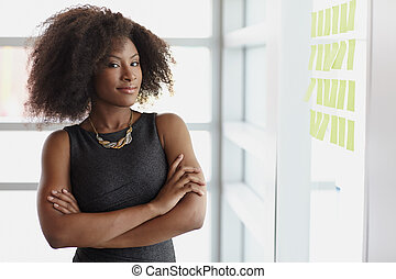 Portrait of a smiling business woman with an afro in bright...