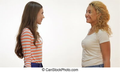 Attractive young girls smile and clap each other palms - Two...