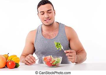 Handsome young man is eating healthy food - Cheerful fit guy...