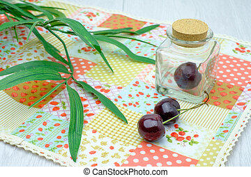 cherries on napery and in glass bottle on white wooden table