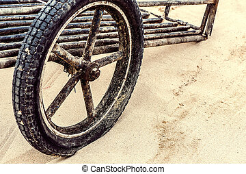 one vintage wooden cartwheel on the sand