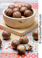 Macadamia on napery and wooden bowl. use opener to unshelled...